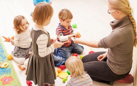 Kinder und ihre Erzieherin spielen mit Bausteinen
