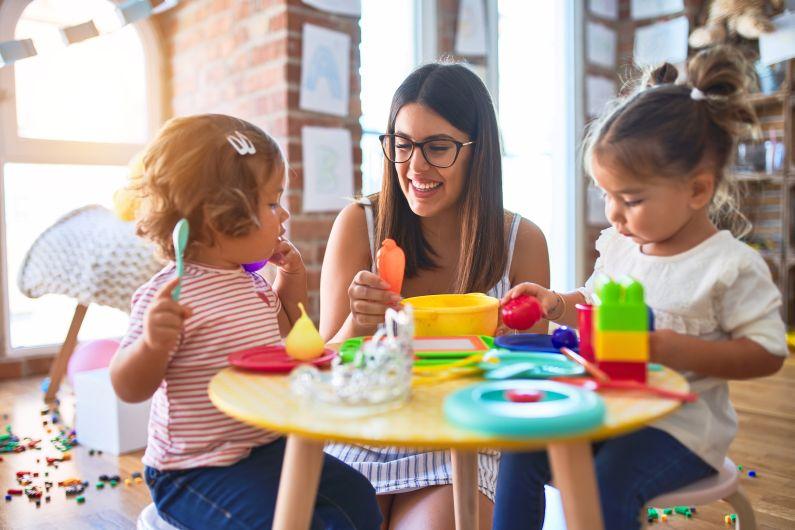 Kinder und Erzieherin spielen