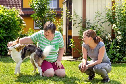Geistig behinderte Frau mit Betreuerin und Hund im Garten